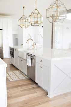 white kitchen, brass accents, one too many pendants (love them!), 'X' detail on the island, pale natural wood floors - sunny beachy and elegant traditional in one design