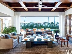 In Clooney's living room, a slipcovered sofa and armchairs and a pair of stools by Casamidy are grouped around a cocktail table by SL Westwood Design; the Alison Berger–designed surveyor's lamp is from Holly Hunt, the striped throw pillows are made of a Ralph Lauren Home fabric, the curtains are of a Holly Hunt linen, and the carpet is by Lawrence of La Brea.