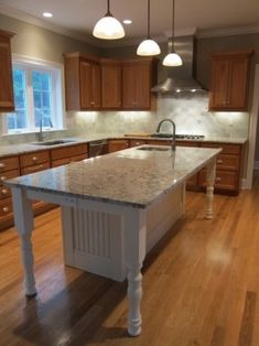 White kitchen island with granite countertop and prep sink.  Island seating for 6 people at bar stools.  Cherry kitchen cabinets, Wolf and Viking appliances and subway pattern tile finish out the space.