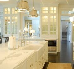 kitchens - Sloane Street Shop Light glass-front white kitchen cabinets white kitchen island marble countertops farmhouse sink polished nickel faucet