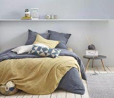 le côté délavé du linge de lit en lit jaune moutarde et gris apporte de la douceur à cette chambre parentale
