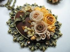 Floral pendant made of antiqued metal and polymer clay.