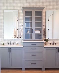 Central bathroom storage tower with identical small vanities lets towel bars go on side of tower.