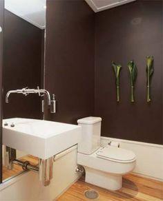 O rodapé branco e alto neutraliza o preto neste lavabo. Por ser um espaço pequeno e de permanência rápida, a ousadia do tom escuro é permitida. Projeto de Roberto Migotto.
