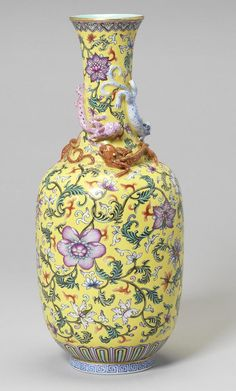 A famille rose bottle vase Daoguang seal mark, 20th century With moulded sinuous dragon encircling the neck and shoulder, painted and gilt with scrolling, entwined flower sprays and foliage on a yellow ground. 33.6cm (13.1/4in) high.