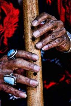 Weathered Navajo hands play a Native American Flute