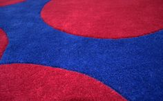 """An abstract styled bespoke rug hand tufted with pure wool in blue and red. It has a pile depth of 15-18mm. Created using the """"sufi"""" design. [close up]"""
