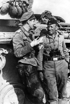 German soldiers (one with an injured hand) have a discussion during a lull in combat on the Eastern Front in the city of Oryol. Oryol was occupied by the Germans on 3 October 1941 and liberated on 5 August 1943 following the Battle of Kursk. The city was almost completely destroyed during the Soviet's effort to retake it. Oryol Oblast, Russia, Soviet Union. 9 July 1942.