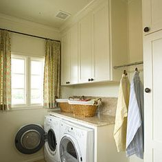 Conceal unsightly laundry detergent, cleaning supplies, and any other products that look like messy clutter in fronted cabinets. A hanging rod was added here to keep drying clothes neat. Baskets create additional storage to keep what's left out sorted and contained. Treat the laundry room as you would any other space by adding cheerful curtains.