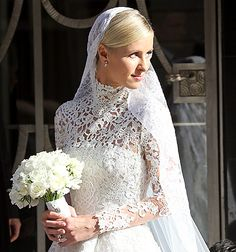 Nicky Hilton leaves Claridges ahead of her wedding on July 10, 2015 in London, England. elegant white Valentino gown with lace overlay. The dress featured a high neck, long sleeves, and a dramatic train. She also wore a long but delicate veil with ornate embroidery.