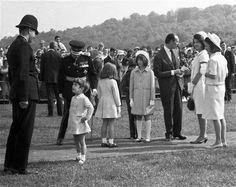 May 14, 1965 -John Kennedy Jr., son of U.S. President John F. Kennedy, talks with a British police officer after the dedication ceremony for the memorial to the late president at Runnymede, Surrey, England. A seven ton Portland stone memorial stands on the historic grounds on an acre of land which became American property, in perpetuity.