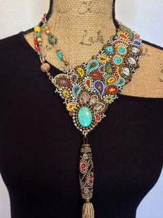 A unique bead embroidery necklace featuring an asymmetrical bib of soft black leather with hundreds of colorful glass seed beads, brass and silver