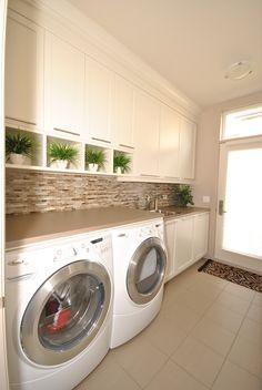 Salle de lavage avec beaucoup de rangement et d'espace comptoir