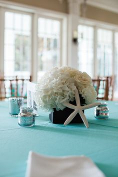 White hydrangea, starfish, and mercury glass votive centerpieces - beach wedding decor idea! {Judy Nuñez Photography}