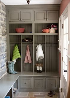 mudroom into garage with window on the wall that is stone