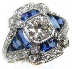 Art Deco sapphire and diamond ring, circa 1910. It is millegrain set with a cushion cut diamond, the surrounding calibre cut sapphires forming a lozenge, diamond dart highlights to the corners and a diamond set outer border. Via Diamonds in the Library. by ruth