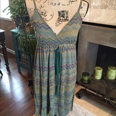 Sun dress 100% nylon and sheer. Hand wash only would recommend. No runs, snags or tears... Great shape. Earthy tones, bohemian in look. Would say a smidgen brighter than reflecting in pics. Size large, more suited to medium. Wore a few times and actually with black leggings, worked great. Mostly greens with some purples, yellows and reds. Not new condition, but great condition. The nylon runs double underneath for lining... Sheer but not super sheer. Straps adjust Sweet Pea Dresses