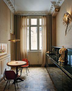 La cuisine, tapissée de toile de jute, est utilisée presque exclusivement pour le petit déjeuner. Studio KO a redessiné la pièce en l'axant sur la fenêtre et en dégageant ainsi un espace pour la buanderie. La crédence est en marbre vert. L'applique a été chinée, tout comme les chaises. La table est une création de Studio KO. Suspension de Florian Schulz.