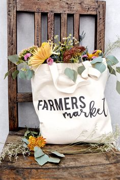 Styled Product Photo The Cotton & Canvas Co. Farmers Market Canvas Tote Bag with Overflowing Flowers Florals Bouquet on Rustic Chair. Fashion Beauty Travel Blogger French Boho Vintage Modern Flatlay. Bespoke Styled Product Photography + Photographer in California and Australia by Chelsea Loren.