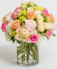 "Cherished Roses Filled with an abundance of premium roses in shades of pink, white and peach and accented with green and white hydrangea, this lush arrangement is sure to ""wow."""
