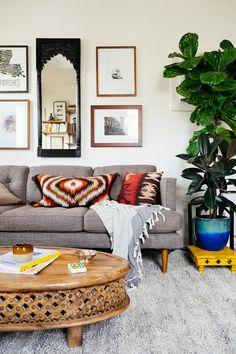 O destaque dessa sala de estar ficou com os detalhes de decoração, tanto com o espelho e os quadros pendurados na parede quanto com as almofadas, bem coloridas e com padronagem étnica. A mesa de madeira e o vaso de plantas deram o toque final na composição.