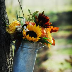 For a Fall Wedding hang galvanized pails filled with sunflowers and other autumnal blooms in the trees surrounding the ceremony.