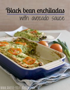 Black bean enchiladas with avocado sauce - cheesy black beans in coriander pesto, soft flour tortillas, creamy avocado sauce and slices of roasted tomato.
