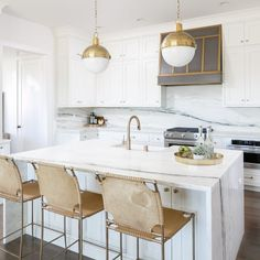 Hudson Valley Lighting Lambert Pendants hang over a white island topped with a white quartz waterfall countertop seating three gold suede barstools and fitted with a farmhouse sink with a Delta Champagne Bronze Trinsic Pull-Down Kitchen Faucet. Kitchen Trends, Small Kitchen, Kitchen Decor, New Kitchen, Home Kitchens, Modern Kitchen Design, Kitchen Remodel Inspiration, Kitchen Renovation, White Kitchen Design