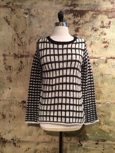 This cool sweater features 2 different black and white checkered patterns on the sleeves and the body. This sweater gives a mod feel while also being casual. Its warm and fuzzy and you'll never wanna take it off!