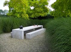 This unique concrete seating area is reminiscent of Stonehenge, but modern, sculptural, and stunning. The variations in height and length create visual appeal, as does the gravel underneath the eating area. The lush garden surrounding the area keeps the space from feeling too industrial.