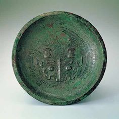 Pan basin with dragon motif, Shang Dynasty (1600-1046 BC).  The surface of this basin is decorated with a coiled dragon, its head, an animal mask in the style of the late Shang period, protruding from the center. Around the rim of the basin are 'kuei' dragon, bird and fish motifs. Casting marks can be found on the reverse side, with traces of six join reinforcements located where the ring foot meets the underside of the vessel.