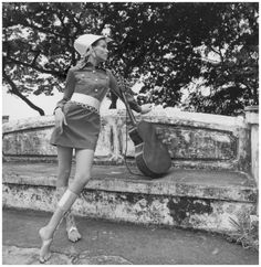 ca. 1968, Honduras — Original caption: Model Veruschka leaning against a stone wall, near a guitar, wearing a navy denim minishirtdress with flap pockets and button placket stitched in white, designed by Ginori; and aluminum 'helmet,' belt, and sandals with knee-high bands by Sant' Angelo; Caribbean island of Bahia.  Photo Franco Rubartelli