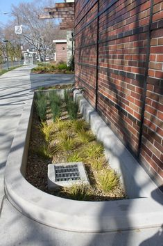 Urban Rainplanter with grating outlet clearly visible. Consider putting gratings on a 1:3 - 1:2 angle to reduce likelihood of blockage by things like plastic bags or leaves that will lie on a flat surface. Walnut Ck Library
