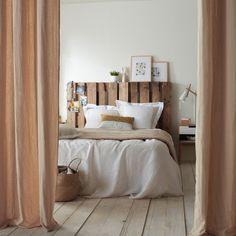 Des palettes pour une tête de lit esprit récup. Vous pourrez personnaliser votre chambre à coucher  grâce à des palettes en bois. Pour cela, utilisez ces dernières comme tête de lit. Laissée à l'état brut sans couche de peinture, la palette de bois ajoutera une touche atypique à cette pièce et sera en harmonie avec un linge de lit en lin.