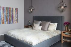 A grey velvet headboard with deep grey textured wallpapered accent wall.