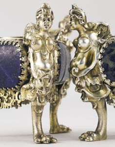 A pair of Italian parcel-gilt silver and lapis lazuli salts, first half 17th century triangular, the paw feet surmounted by caryatids, the sides mounted with a lapis lazuli panel above an openwork foliate apron, the tops engraved with flowers at angles, with removable silver-mounted lapis cellars, with alterations apparently unmarked length 3 1/2 in.