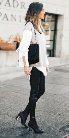Alba Hervas + tight leather leggings + sleek black boots + layered white blouse + cutaway sleeves + beige top + lush black handbag. Brands not specified. Spring.