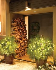 The front door of Sarah's house features square wreaths.    A festive winter scene of stacked firewood and giant pine boughs, decorated with reflective silver balls and warm white lights, sets the tone before guests set foot inside. This look is a nice balance between modern and traditional Christmas style.