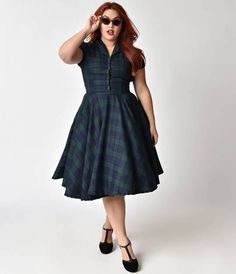 Prepare for some tasty tartan, dames! Crafted in a soft woven blend, the Mona is a gorgeous plus size swing cast a marvelously vintage silhouette of dark navy and emerald plaid. The dainty button up bodice features matching buttons that lead up to a class