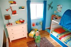 Bright, colorful boys room. Cars and trucks and planes. Love the toy cars on shelves on the wall.