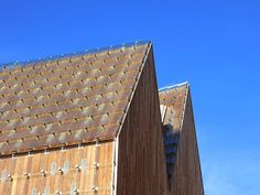 Overlapping glass shingles wrap the roof in an elegant deconstruction of traditional building techniques. Chinks of light are admitted into the hall through the tiny openings in the timber superstructure