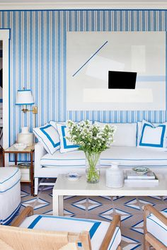 The striped walls and crisp white seating in the master sitting room are upholstered in weather-resistant fabric and piped in marine blue trim.