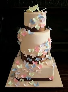 Butterfly Wedding Cake by Sweet Cupcakes & Treats -This cake is a three tier, 4 layer cake of blush pink fondant with chocolate brown ribbon accents. The entire cake was then wrapped in a kaleidoscope of butterflies, and topped with a pair of ivory sugarpaste butterflies highlighted with ivory lustre.