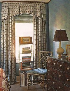 Nicely restrained window treatment with an inverted pleat arched valance with banding and nailheads & soft panels