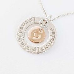 The two tone sterling silver family circle pendant with 14k gold fill heart charm in the center is a meaningful way to capture each child's name. Makes a thoughtful Mother's Day, Christmas or Birthday gift idea for a deserving Mom or Grandmother. Sterling silver circle washer necklace with 1 2 3 kids names stamped around ring and gold fill heart disc hangs in the center - Mother's Day gift ideas for Mom or Grandmother Family Necklace, Name Necklace, Washer Necklace, Family Circle, Heart Of Gold, Personalized Jewelry, Heart Charm, Sterling Silver Rings, Fill