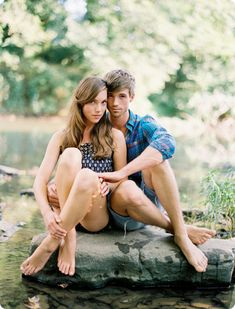 Cute for engagement photo! sitting on a rock in the river.