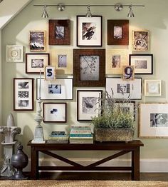 Mismatched framed photo collage in entryway over a low table... I love this and would totally do it if there wasn't a hallway at our front door.