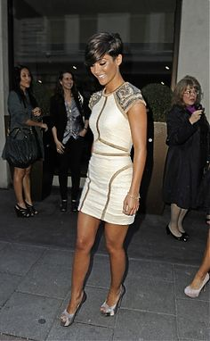 This is a unique outfit choice by Frankie Sandford but it suits her well. Her beige dress with golden hem patters and gray heels show off her brilliant figure.