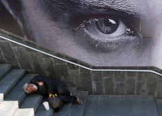 A homeless man sleeps on stairs in front of a billboard in the center of the Ukrainian capital Kyiv. (AFP)