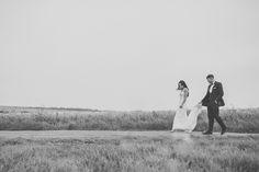 Bride & Groom walking hand in hand, by a field full of wheat.